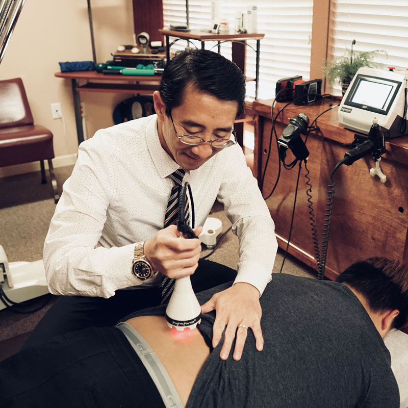 Dr. Dinh Le using a device for deep tissue laser therapy